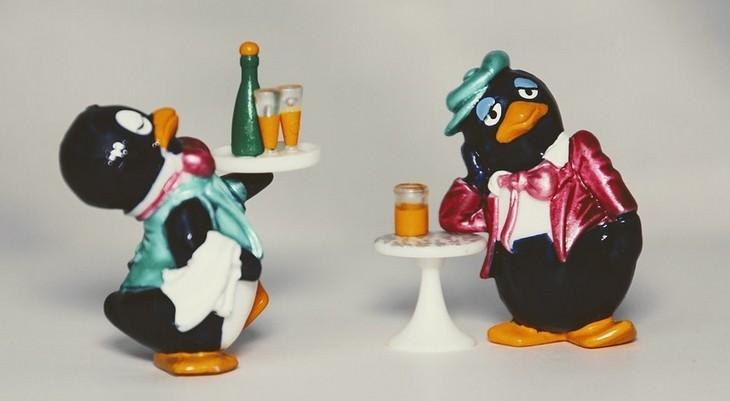 טיפים לאירוח: בובה של פינגווין מגישה משקה לבובה אחרת