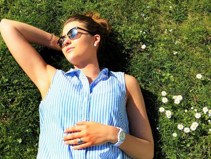 דרכי הגנה מפני סרטן העור: אישה עם משקפי שמש שוכבת על דשא