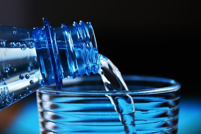 מים נמזגים מתוך בקבוק לכוס