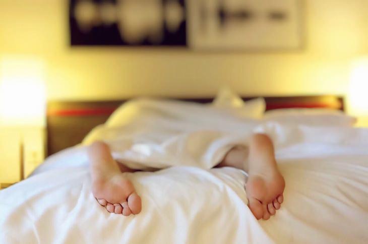 יתרונות השינה בעירום: כפות רגליים מבצבצות מבעד לסדינים במיטה