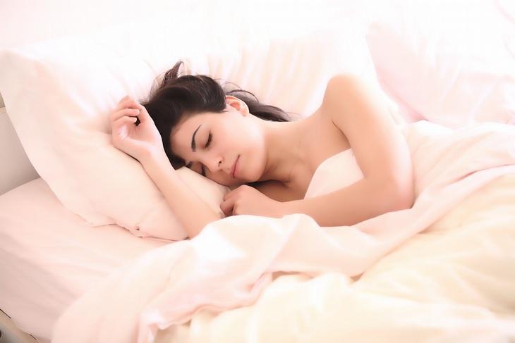 יתרונות השינה בעירום: אישה ישנה במיטה
