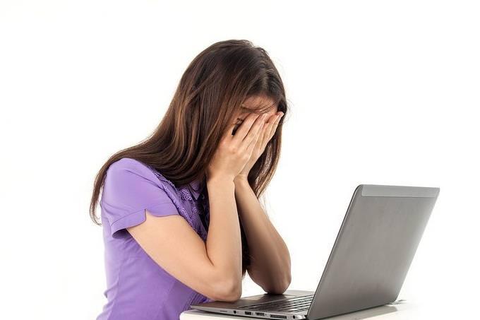 אישה מחזיקה את פניה מול מחשב נייד