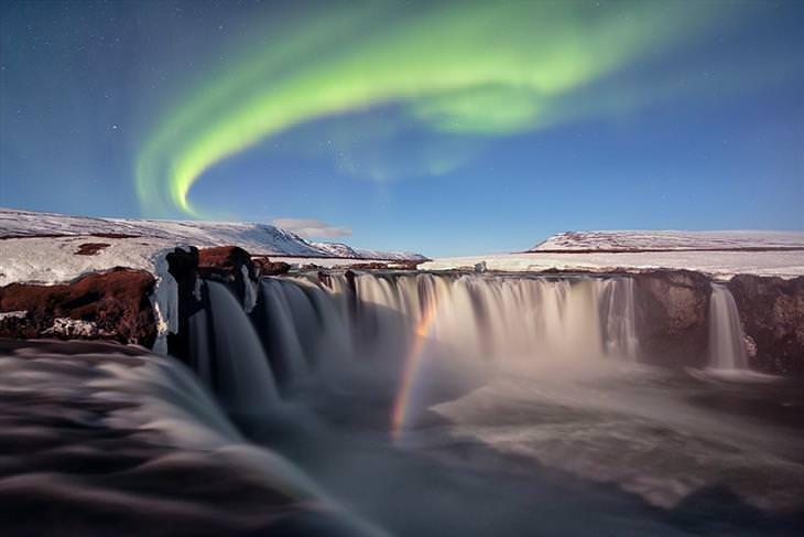 תמונות מתחרות צילום טבע: אורות הזוהר הצפוני מעל מפל עם קשת בענן שעוברת דרכו