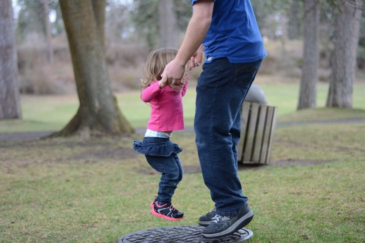 טיפים להורות מאושרת: אב וביתו קופצים על מתקן בגן שעשועים