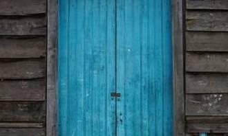 דלת בצבע טורקיז לצד שלבי עץ