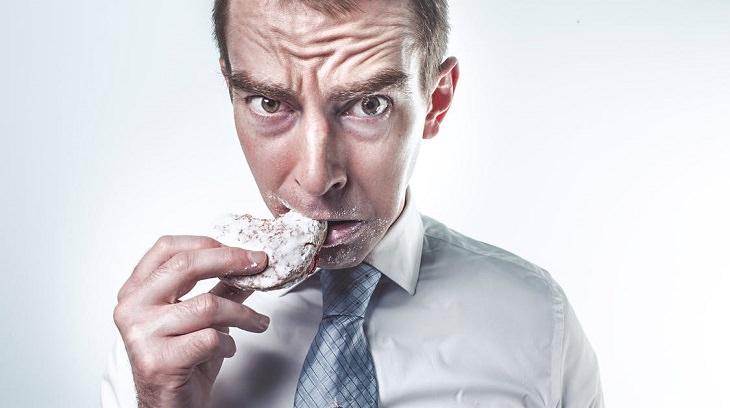 גבר אוכל עוגייה עם מבט מבולבל