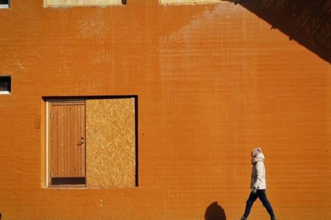 אדם צועד לצד קיר כתום