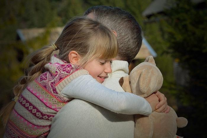 ילדה עם דובי מחבקת את אבא שלה