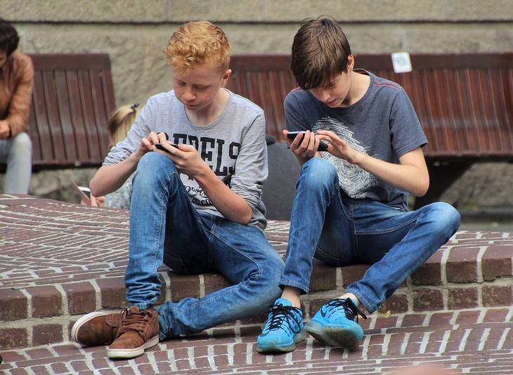 ילדים יושבים על מדרכה ומשחקים בטלפונים ניידים