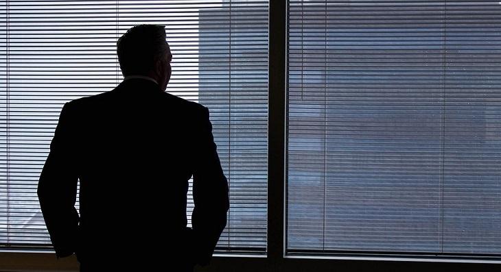 איש בחליפה עומד מול חלון