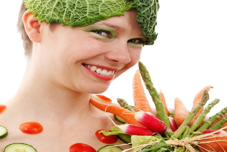 טעויות במעבר לצמחונות או טבעונות: אישה מחייכת, פניה וגופה מכוסים בירקות