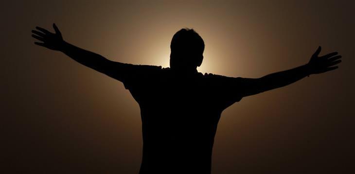 המדע שמאחורי הדרך הנכונה להצלחה: צללית של אדם עומד מול השקיעה עם ידיו באוויר
