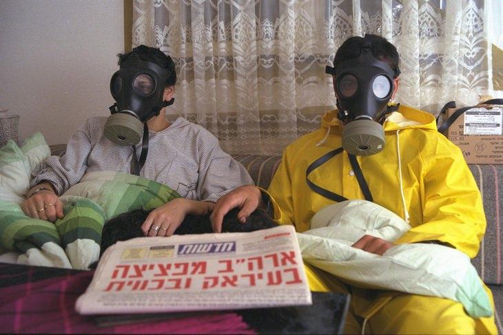 """מלחמת המפרץ: שני אנשים יושבים עם מסכות אב""""כ בחדר האטום"""