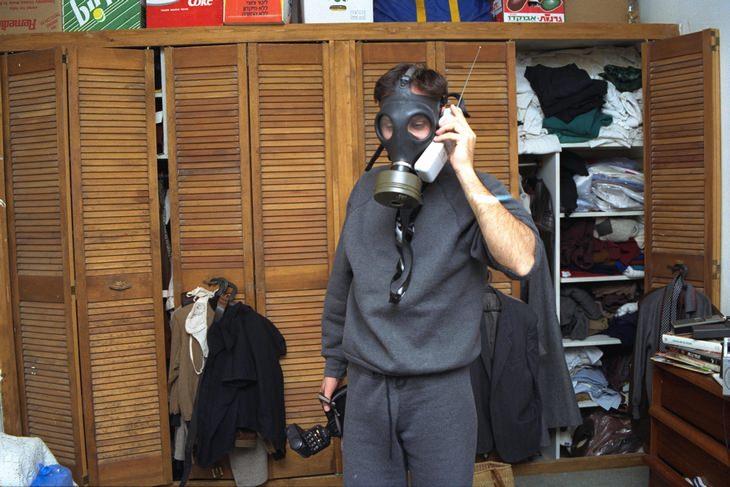"""מלחמת המפרץ: גבר עם מסכת אב""""כ משוחח בחדר שינה בטלפון"""