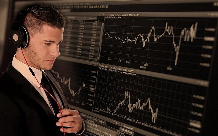 מדריך למתעשר: יועץ השקעות על רקע מסכי מחשב