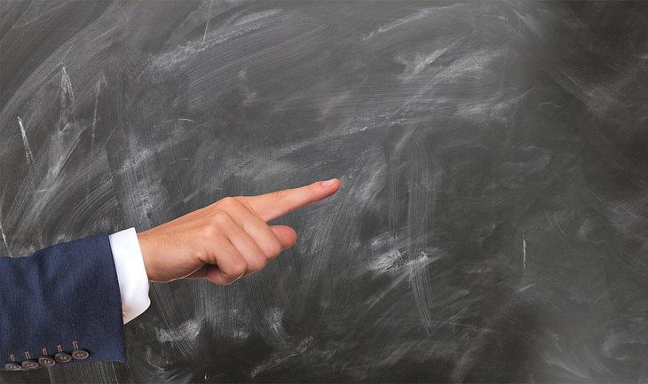 זכויות של הורים ותלמידים: יד של אדם מצביעה לצד מול לוח גירים