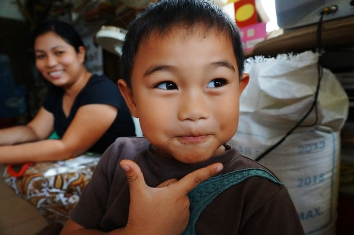 התמודדות עם דיבור מביך של ילדים: ילד מרים יד מתחת לפניו ומחייך