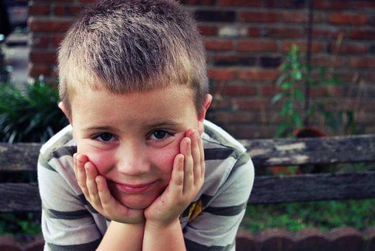 זכויות של הורים ותלמידים: ילד מחזיק את פניו בידיו ומסתכל לכיוון המצלמה