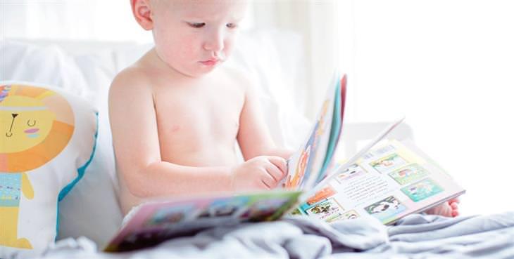 שאלות נפוצות ותשובות בנוגע לתהליך גמילה מחיתולים: ילד יושב במיטה ומסתכל על חוברת