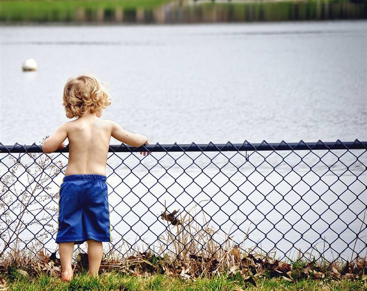 איך לגדל ילדים שיודעים לחשוב בצורה יצירתית: ילד עומד מול נהר ומסתכל עליו מעבר לגדר