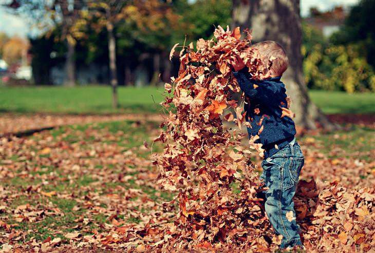 איך לגדל ילדים שיודעים לחשוב בצורה יצירתית: ילד משליך עלי שלכת לאוויר