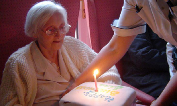 הבדל בין אלצהיימר לזקנה: אישה מבוגרת ועוגת יום הולדת עם נר אחד