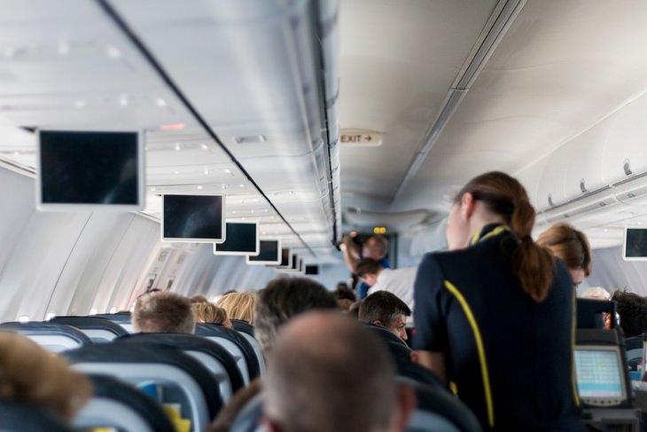 אסור לעשות בטיסה: דיילת עומדת סמוך לנוסעים במטוס