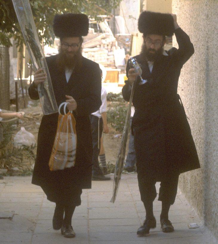 תמונות נוסטלגיות של חגי תשרי: אנשים דתיים עם פריטים לסוכות בידיהם