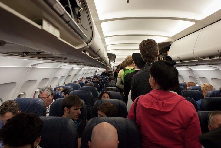 אסור לעשות בטיסה: נוסעים עומדים במעבר של מטוס נוסעים לצד נוסעים במושבים