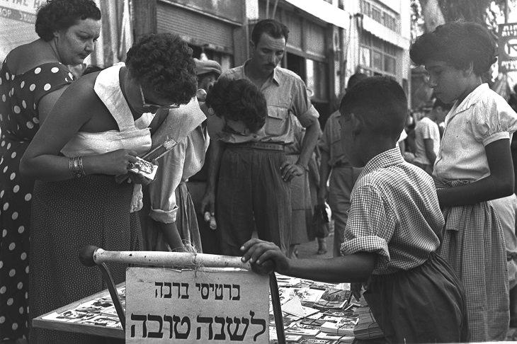 תמונות נוסטלגיות של חגי תשרי: אנשים מסתכלים על כרטיסי ברכה בדוכן באמצע הרחוב