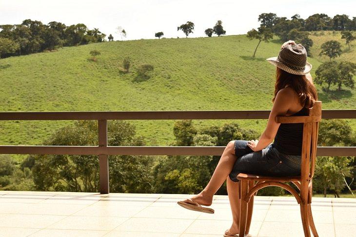 לאהוב את עצמנו: אישה חובשת כובע יושבת במרפסת ומביטה על נוף של דשא ועצים