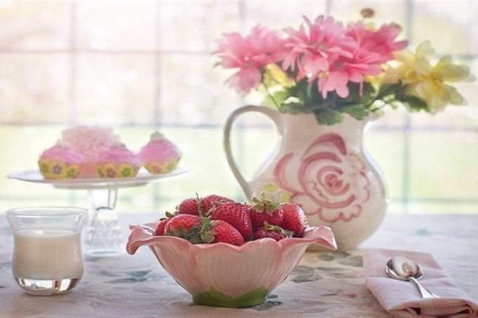 שולחן ערוך עם קערת תותים, כוס חלב ואגרטל עם פרחים