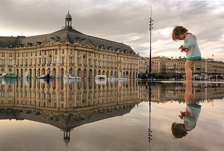 נוף עירוני משתקף בשלוליות: ילד עומד על שלולית בבורדו, צרפת