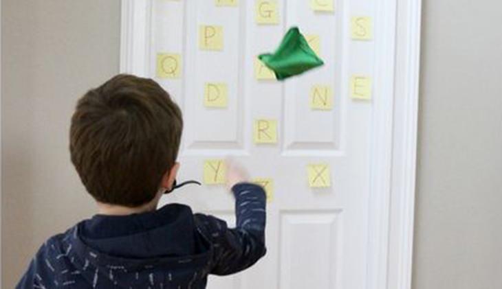 משחקים ביתיים שיגרמו לילדים להפעיל את הגוף והמוח: ילד זורק שקיות חול לאותיות שמודבקות על דלת