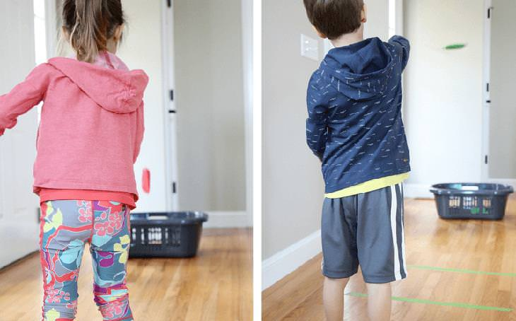 משחקים ביתיים שיגרמו לילדים להפעיל את הגוף והמוח: ילדים זורקים חפצים לתוך סל כביסה