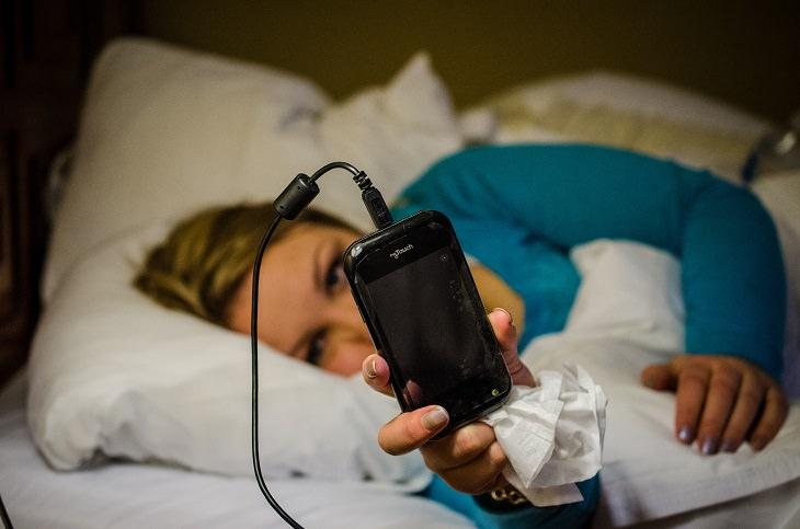 איך להתאושש משנת לילה רעה: אישה במיטה מתבוננת בטלפון הנייד שלה