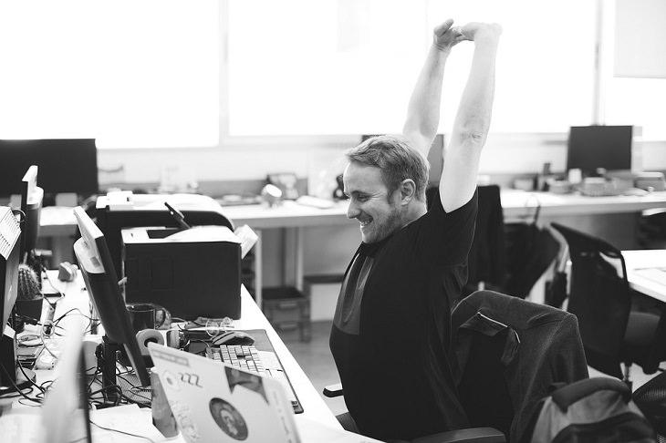 שיר על הטוב שברע: בחור מחוייך מותח ידיים במקום העבודה