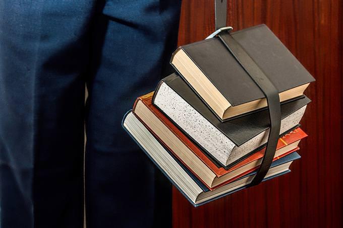 איש מחזיק אסופת ספרים בעזרת חגורה