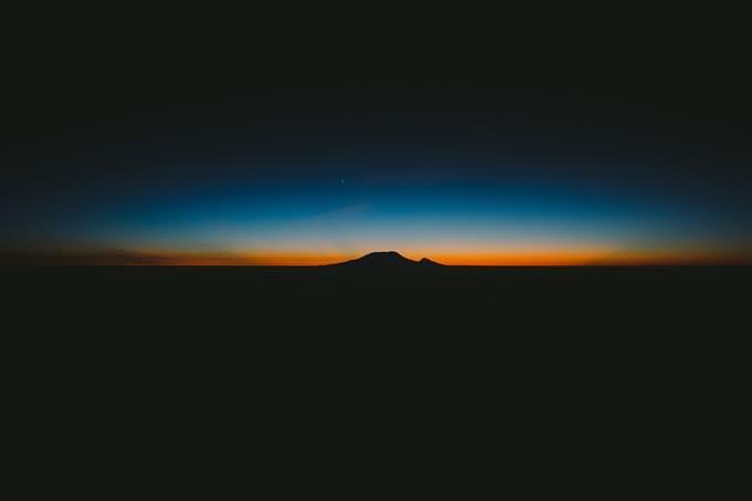 אור כתום על רקע השמיים וצל הרים