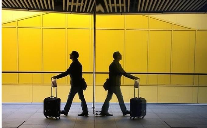 בחן את עצמך: דמות אדם עם מזוודה משוכפלת מול מראה